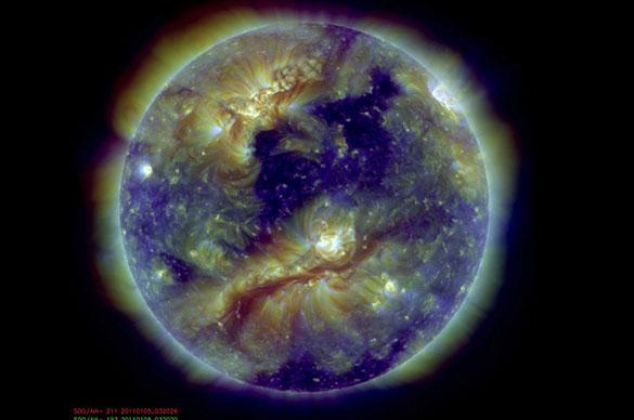 """Debido a su temperatura del orden del millón de grados, la atmósfera solar emite ondas electromagnéticas en el rango Ultravioleta (UV) y X. Esta colorida imagen de la atmósfera solar, tomada por el instrumento Atmospheric Imaging Assembly (AIA) a bordo de la nave espacial Solar Dynamics Observartory (SDO), es una superposición de exposiciones en tres filtros Extremo-UV sensibles al rango 1 a 2 millones de grados. Las zonas más brillantes de esta imagen revelan el plasma más caliente atrapado en intensos, pero invisibles, campos magnéticos cerrados. Las zonas oscuras, que contienen plasma más frío, se denominan """"agujeros coronales"""" y son regiones con campo magnético abierto. Estos """"agujeros"""" son la fuente del """"viento solar"""" que eventualmente impacta en la Tierra. Imagen cortesía del equipo del instrumento espacial AIA/SDO."""